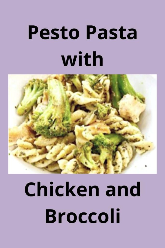 Rotini pasta noodles mixed with pesto hummus, stalks of broccoli and chunks of chicken with a white background